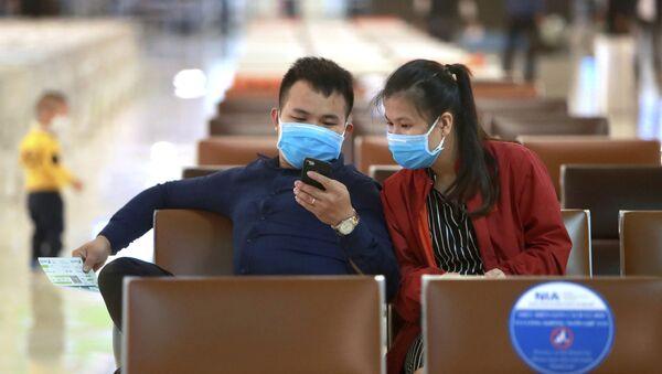 Hành khách đeo khẩu trang chờ chuyến bay tại sân bay Hà Nội, Việt Nam. - Sputnik Việt Nam