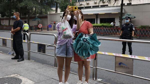 Các cô gái tđang chụp ảnh tự sướng bên ngoài Lãnh sự quán Hoa Kỳ ở Thành Đô, Trung Quốc. - Sputnik Việt Nam