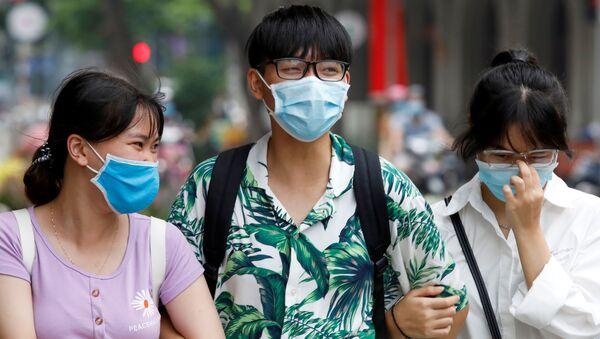 Người dân đeo khẩu trang bảo vệ trên đường phố Hà Nội. - Sputnik Việt Nam
