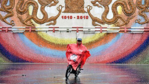 Người đàn ông đi xe máy trong trận mưa bão ở Hà Nội - Sputnik Việt Nam