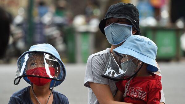 Mẹ và con xếp hàng chờ xét nghiệm coronavirus tại một trung tâm test nhanh ở Hà Nội, Việt Nam. - Sputnik Việt Nam