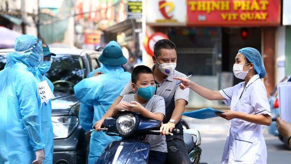 Nhân viên y tế hướng dẫn người dân xếp hàng theo phường đã đăng ký. - Sputnik Việt Nam