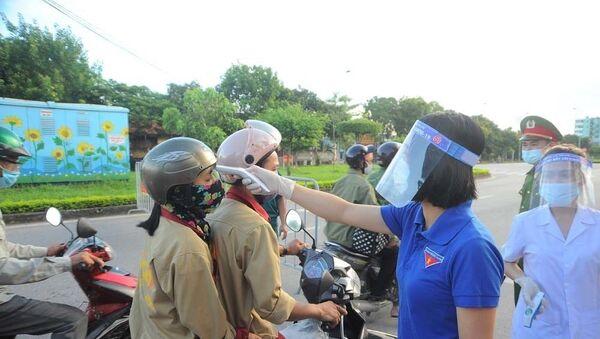 Đo nhiệt độ cho người dân tại chốt kiểm soát trên đường Trường Chinh lối vào thành phố Hải Dương. - Sputnik Việt Nam