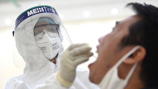 Nhân viên y tế của quận Cầu Giấy, Hà Nội tiến hành lấy mẫu dịch hầu họng để xét nghiệm bằng phương pháp RT-PCR của người dân từ Đà Nẵng trở về. - Sputnik Việt Nam