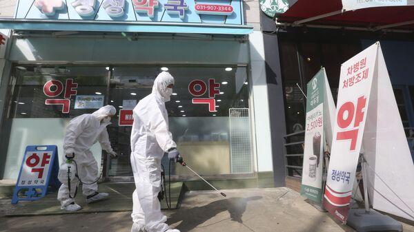 Nhân viên khử trùng trước một hiệu thuốc ở Hàn Quốc - Sputnik Việt Nam