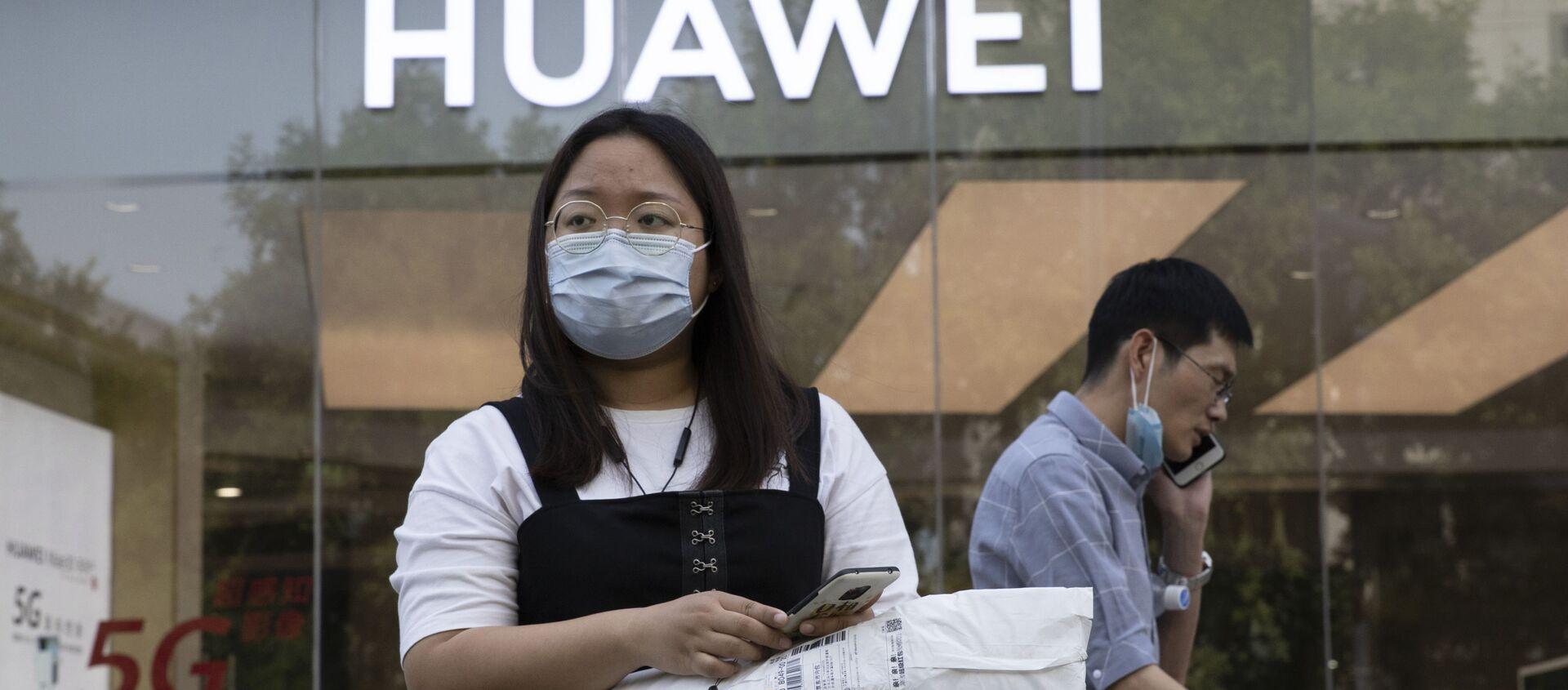 Cô gái đeo khẩu trang y tế trên nền của cửa hàng Huawei. Bắc Kinh - Sputnik Việt Nam, 1920, 16.04.2021