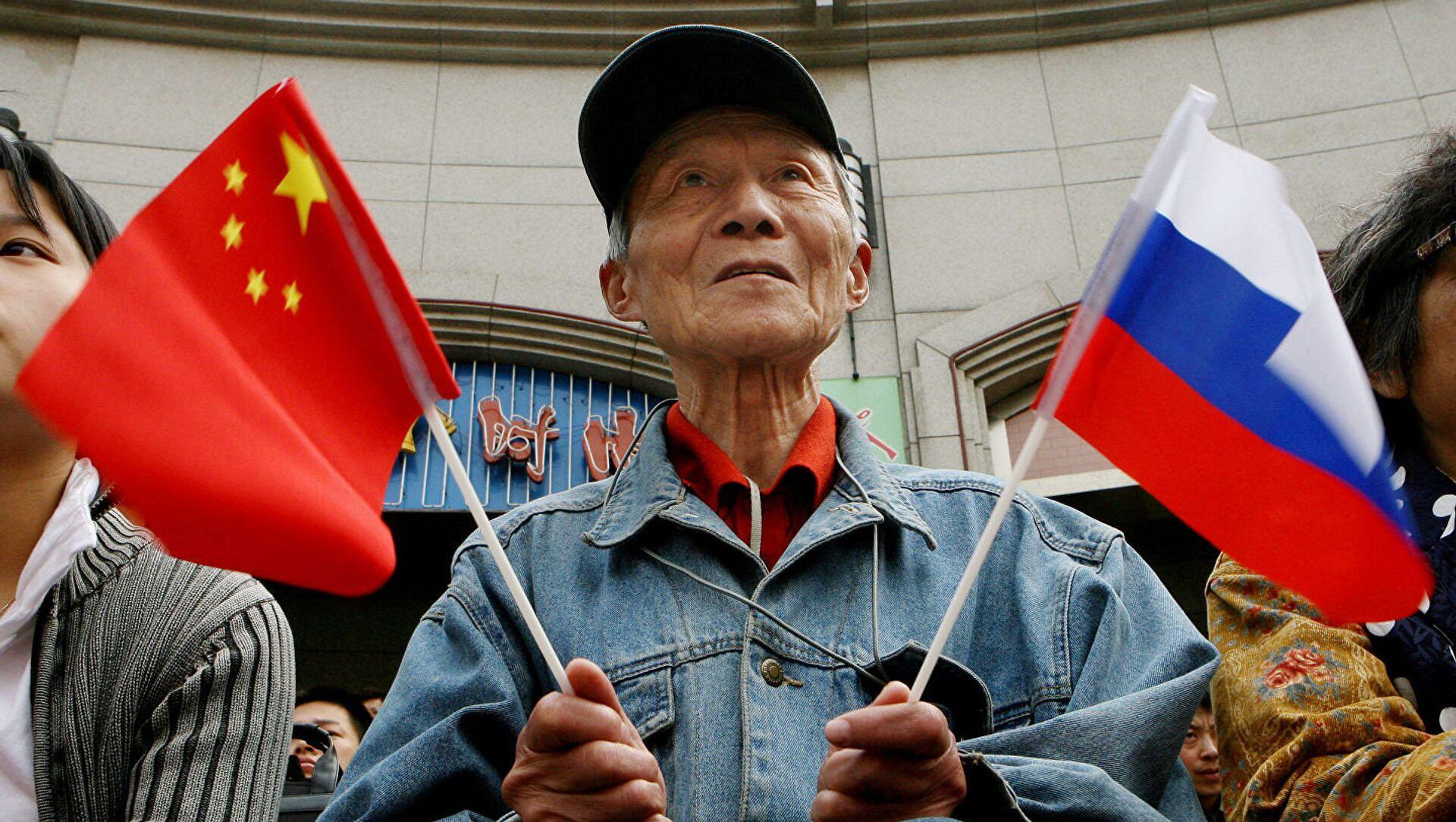 Người cao tuổi cầm cờ Trung Quốc và Nga - Sputnik Việt Nam, 1920, 29.04.2021