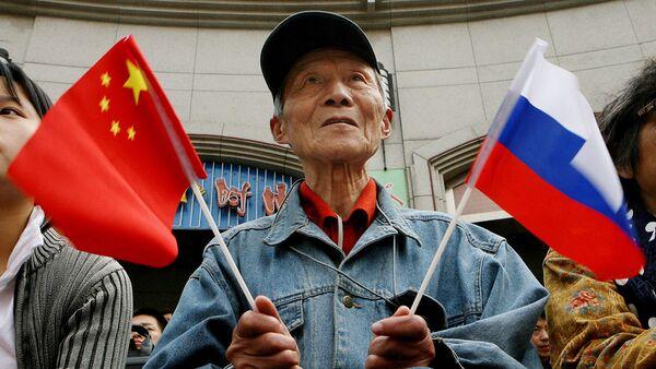 Người cao tuổi cầm cờ Trung Quốc và Nga - Sputnik Việt Nam