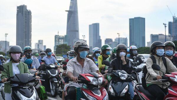 Người đeo khẩu trang đi xe máy  trước đèn hiệu giao thông ở Việt Nam. - Sputnik Việt Nam