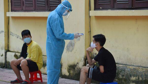 Nhân viên y tế mặc quần áo bảo hộ kiểm tra thân nhiệt của một người ở Hà Nội. - Sputnik Việt Nam