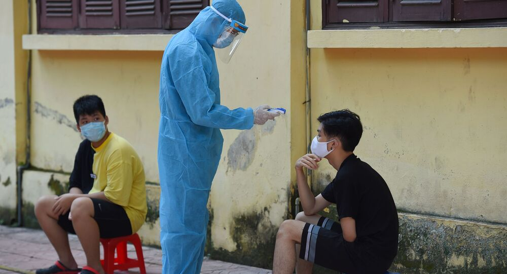 Nhân viên y tế mặc quần áo bảo hộ kiểm tra thân nhiệt của một người ở Hà Nội.