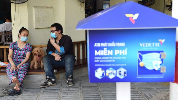 Những người ngồi trong quán cà phê cạnh máy bán khẩu trang miễn phí ở Hà Nội. - Sputnik Việt Nam