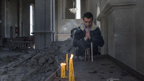 Một cư dân địa phương trong toà giáo đường bị đạn pháo phá hủy ở thành phố Shushi, Karabakh - Sputnik Việt Nam