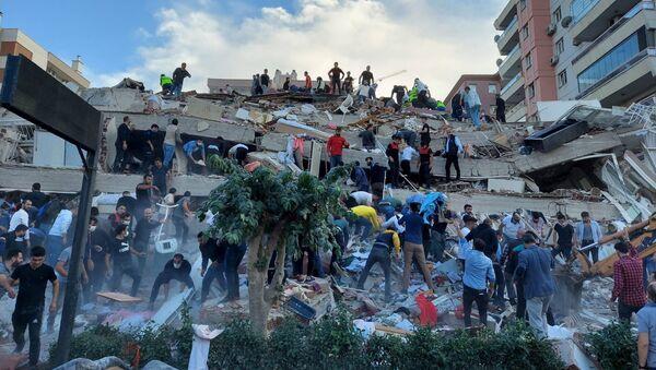 Lực lượng cứu hộ và cư dân địa phương sơ tán nạn nhân vụ sập nhà do hậu quả động đất ở tỉnh Izmir, Thổ Nhĩ Kỳ. - Sputnik Việt Nam