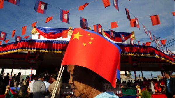 Người phụ nữ Campuchia với lá cờ Trung Quốc đi qua cầu Hữu nghị Campuchia-Trung Quốc trong lễ khai trương cầu này ở Tahmao - Sputnik Việt Nam