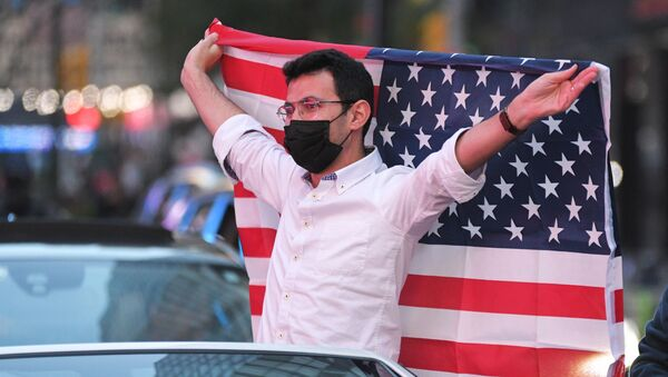 Người đàn ông với lá cờ Mỹ tại Quảng trường Thời đại ở New York sau tin ứng cử viên đảng Dân chủ Joseph Biden giành chiến thắng trong cuộc bầu cử tổng thống Mỹ - Sputnik Việt Nam