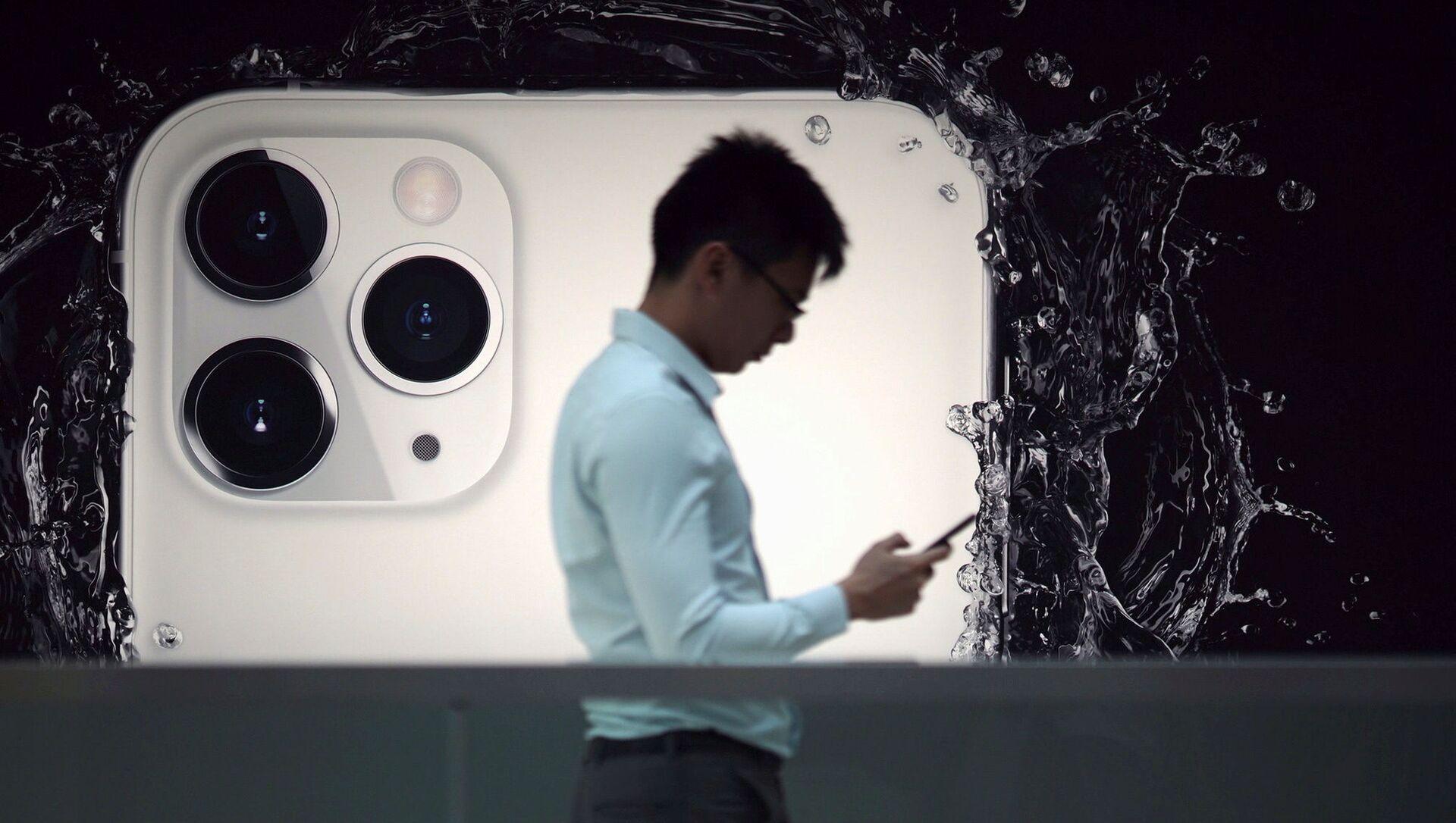 Người đàn ông trên nền quảng cáo iPhone 11 Pro - Sputnik Việt Nam, 1920, 21.07.2021
