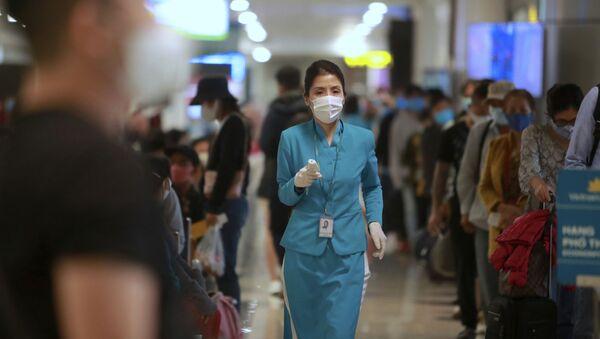 Nhân viên hàng không cầm nhiệt kế tại sân bay Hà Nội, Việt Nam - Sputnik Việt Nam