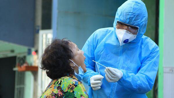 Nhân viên y tế lấy mẫu xét nghiệm người dân trong khu vực Lô E, Lò Gốm (Phường 7, Quận 6). Ảnh: Đinh Hằng - TTXVN - Sputnik Việt Nam