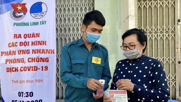 Chiến sĩ dân quân phường Linh Tây (Quận Thủ Đức) phát khẩu trang, dung dịch rửa tay miễn phí cho người dân. - Sputnik Việt Nam