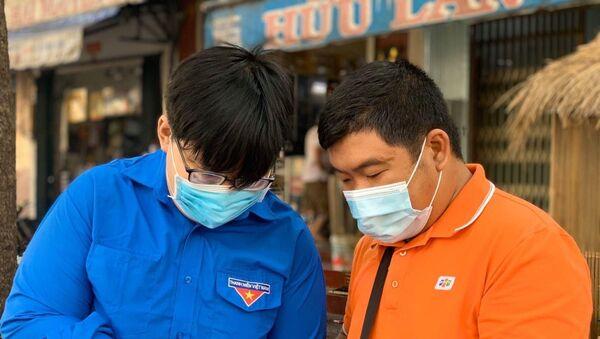 Đoàn viên thanh niên tình nguyện hướng dẫn người dân cài đặt ứng dụng Bluezone trên điện thoại. - Sputnik Việt Nam