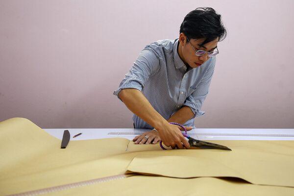 Doanh nhân Nguyễn Đức Lộc đang nghiên cứu tạo mẫu cổ phục trên cơ sở mô-tip truyền thống ở Hà Nội  - Sputnik Việt Nam