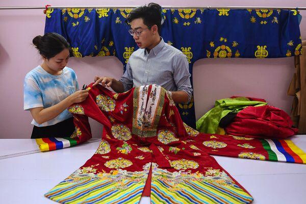 Doanh nhân Nguyễn Đức Lộc kiểm tra các mẫu cổ phục trên cơ sở mô-tip truyền thống ở Hà Nội  - Sputnik Việt Nam