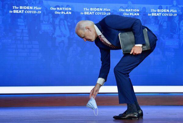 Ứng cử viên tổng thống Mỹ Joe Biden nghiêng người trên chiếc khẩu trang y tế bị rơi - Sputnik Việt Nam