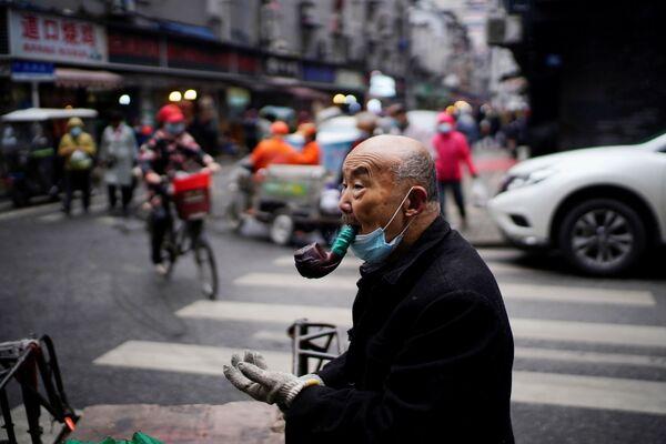 Người đàn ông lớn tuổi hút tẩu trong chợ đường phố ở Vũ Hán - Sputnik Việt Nam