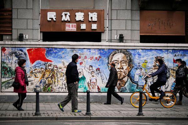 Những người mang khẩu trang trước bức vẽ graffiti ở Vũ Hán, gần một năm sau khi đại dịch bắt đầu - Sputnik Việt Nam