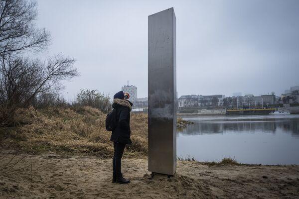Một người phụ nữ bên tảng kim loại nguyên khối xuất hiện bên bờ sông Vistula ở thủ đô Warsaw, Ba Lan - Sputnik Việt Nam