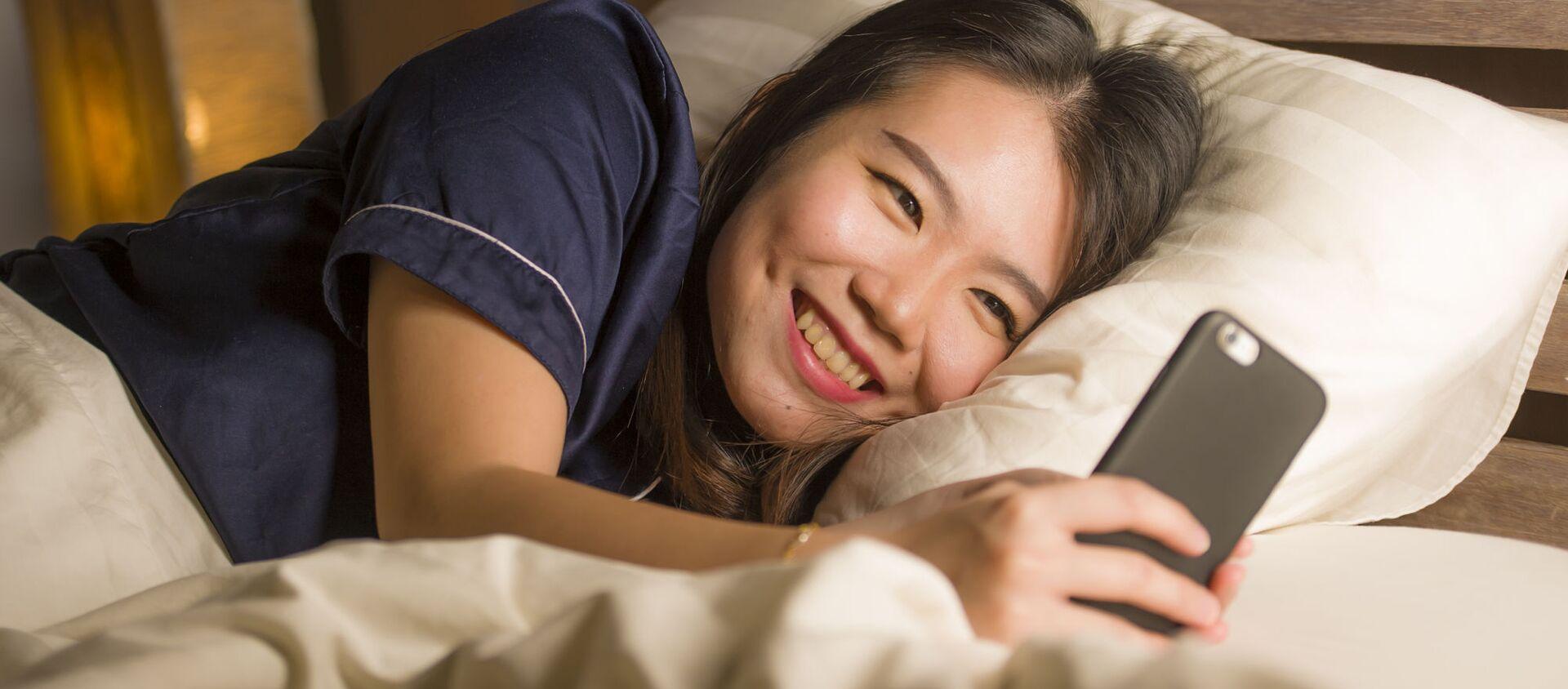 Cô gái Nhật Bản trẻ tuổi đang cười khi sử dụng điện thoại thông minh - Sputnik Việt Nam, 1920, 11.03.2021