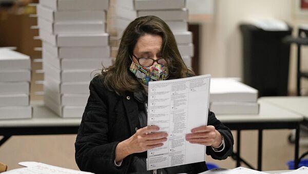 Một nhân viên đeo mặt nạ bảo vệ tại một điểm bỏ phiếu ở Hoa Kỳ ở Thành phố Salt Lake - Sputnik Việt Nam