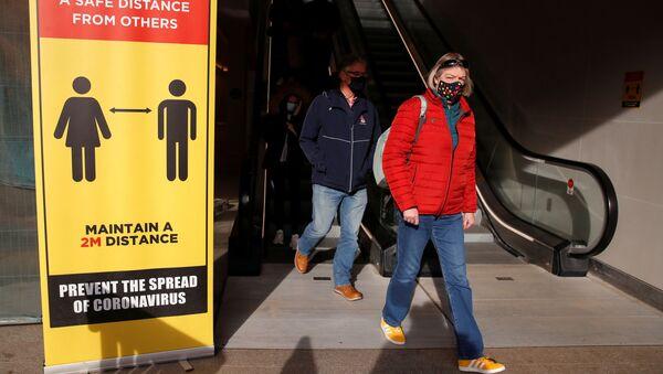 Những người đeo mặt nạ bảo hộ đi ngang qua một biển báo ngăn cách xã hội ở Coventry, Vương quốc Anh - Sputnik Việt Nam