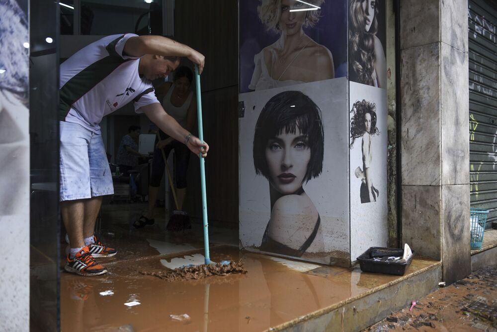 Người đàn ông thu dọn bùn bẩn trong cửa hàng sau trận lụt ở Belo Horizonte, Brazil
