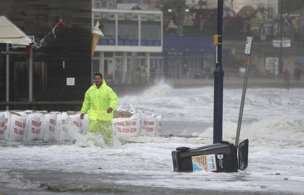 Người đàn ông trên bờ sông ngập lụt ở Swanage sau cơn bão Alex, Vương quốc Anh