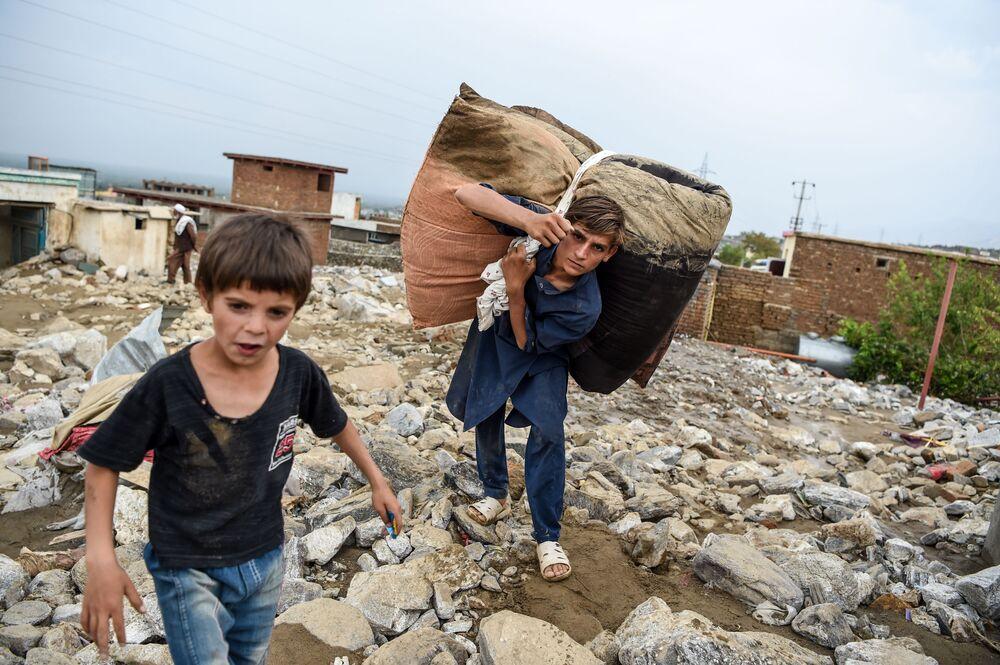 Thanh niên cứu những đồ đạc còn sót lại từ những ngôi nhà đống đổ nát sau trận lũ quét ở Charikar, tỉnh Parwan, Afghanistan