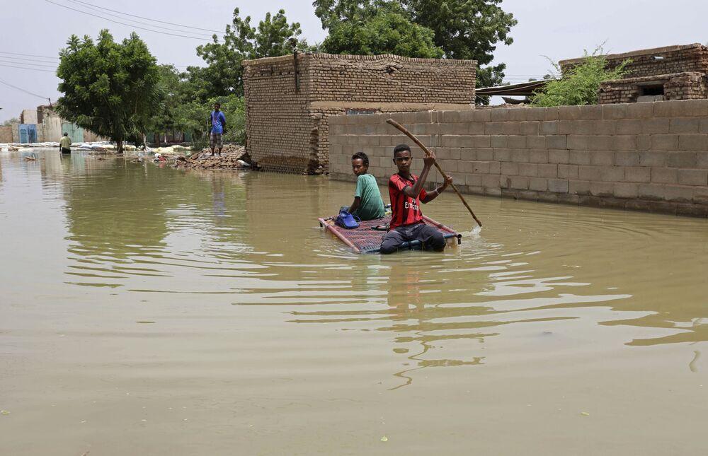 Thiếu niên chống bè bơi trên đường phố ngập lụt ở Salmaniya, Sudan