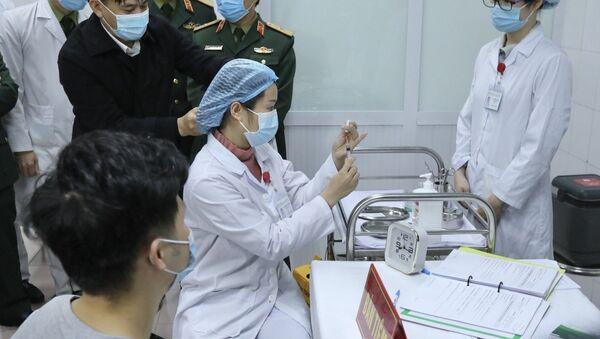 Bác sĩ chuẩn bị tiêm mũi vaccine Nanocovax ngừa COVID-19 đầu tiên cho tình nguyện viên. Đây là vaccine đầu tiên của Việt Nam được đưa vào thử nghiệm lâm sàng. - Sputnik Việt Nam
