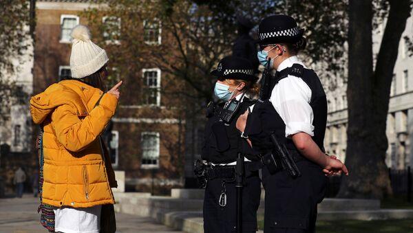 Cảnh sát đeo khẩu trang và những người phản đối lệnh hạn chế ở London, Anh. - Sputnik Việt Nam