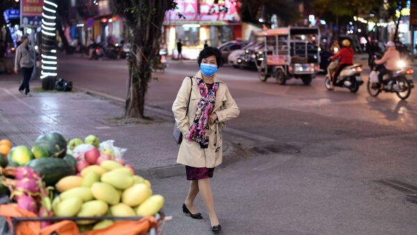 Người phụ nữ đeo khẩu trang trên phố Hà Nội. - Sputnik Việt Nam