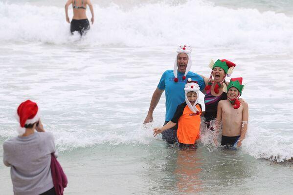 Những người mặc trang phục Giáng sinh chụp ảnh đêm Giáng sinh tại bãi biển Bondi ở Sydney, Australia - Sputnik Việt Nam