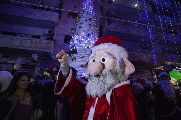 Người đàn ông hóa trang thành ông già Noel trong lễ Giáng sinh ở thành phố Qamishli, Syria - Sputnik Việt Nam