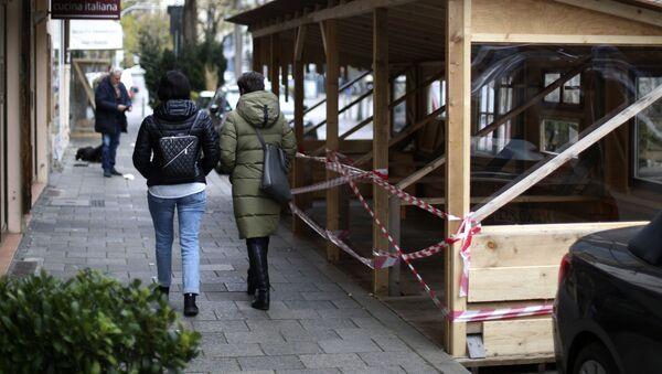 Mọi người đi ngang qua một nhà hàng đã đóng cửa trong đợt phong tỏa ở Munich. - Sputnik Việt Nam