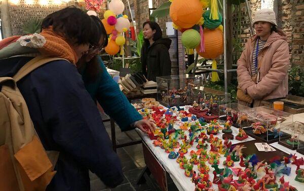 Các bạn trẻ thích thú trước các con tò he màu sắc, nhiều hình dáng, được các thợ thủ công nặn khéo léo. - Sputnik Việt Nam