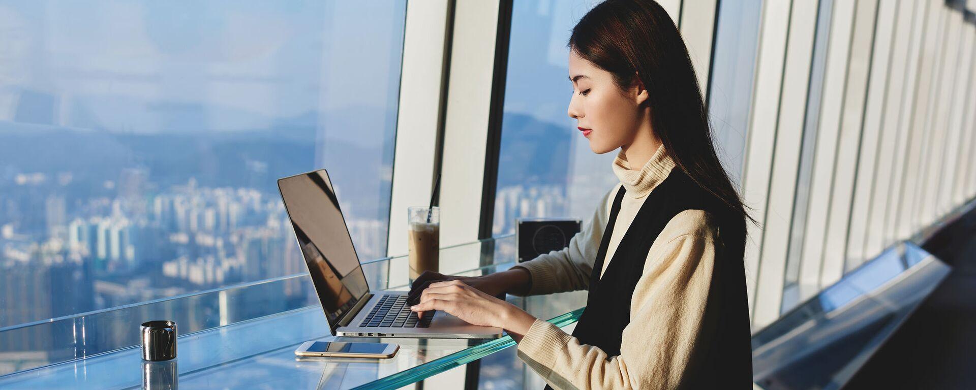 Cô gái châu Á đang làm việc trên máy tính xách tay. - Sputnik Việt Nam, 1920, 17.06.2021