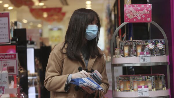 Cô gái đeo khẩu trang trong cửa hiệu mỹ phẩm. - Sputnik Việt Nam
