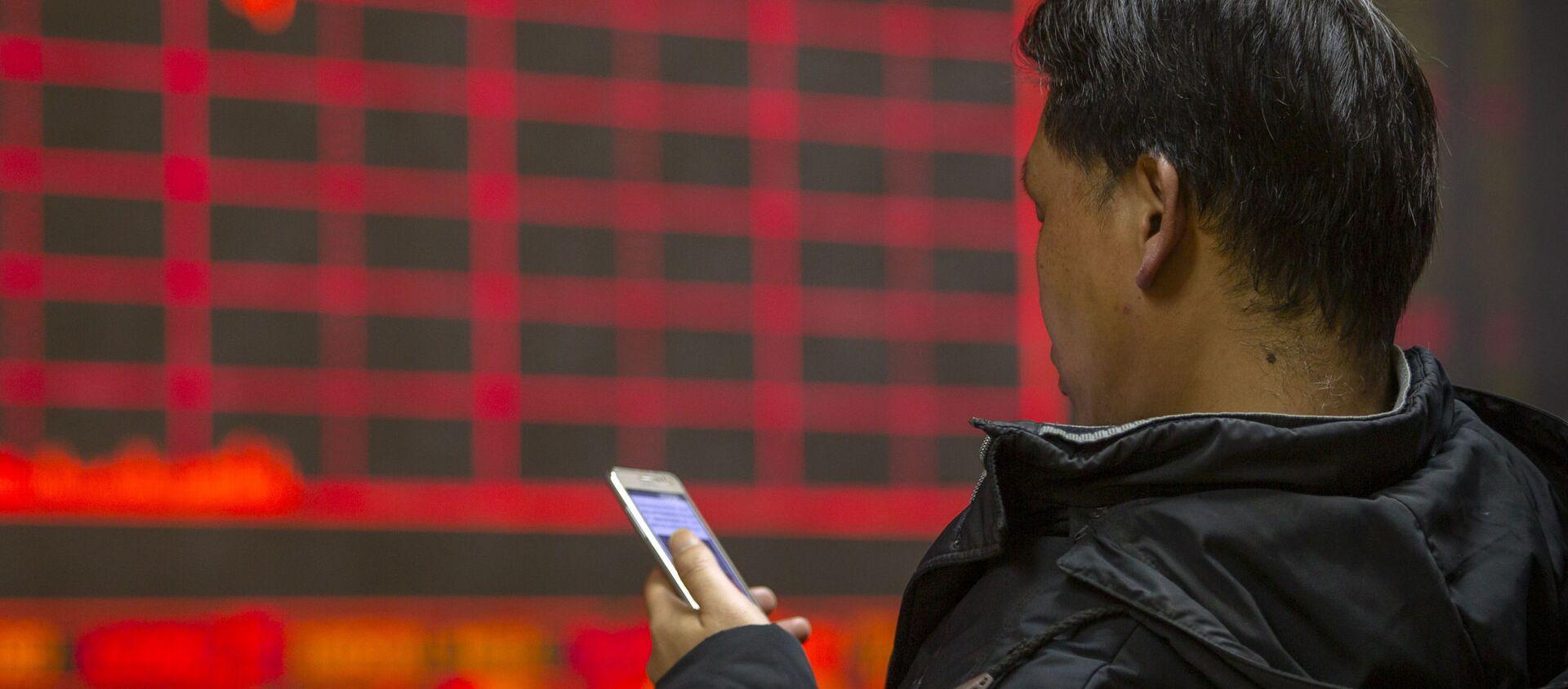 Người đàn ông theo dõi giá cổ phiếu tại một công ty môi giới ở Bắc Kinh - Sputnik Việt Nam, 1920, 08.04.2021