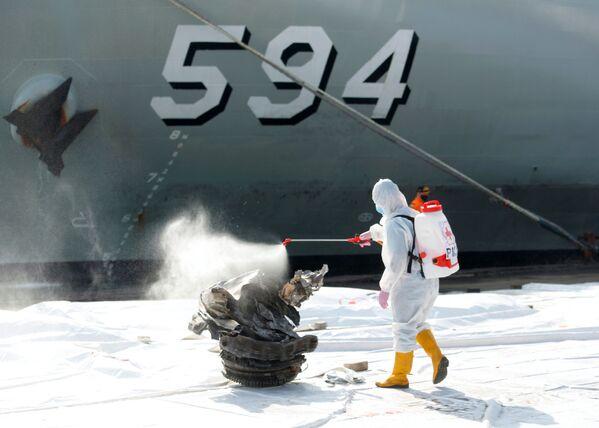 Nhân viên Hội Chữ thập đỏ phun chất khử trùng lên mảnh tuabin máy bay hãng Sriwijaya Air bị rơi ở biển Java - Sputnik Việt Nam