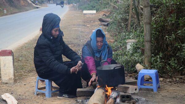 Người dân sinh sống dưới chân đèo Pha Đin, cạnh QL6 đốt lửa sưởi ấm, chống chọi với giá lạnh. - Sputnik Việt Nam